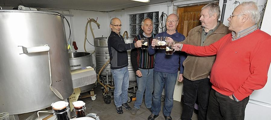 Prosit: Fünf Hobbybrauer stoßen vor der  Garagenanlage des Zirndorfers Klaus Schober (Zweiter von links) an. Manchen Hausbrauern genügt auch schon ein kleiner Kessel in der eigenen Küche.
