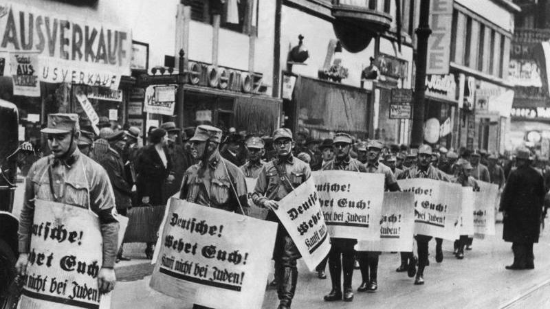 Männer der SA im Jahr 1938 bei einem Hetzmarsch gegen die jüdische Bevölkerung Deutschlands. Die zur Schau getragenen Plakate tragen die Aufschrift