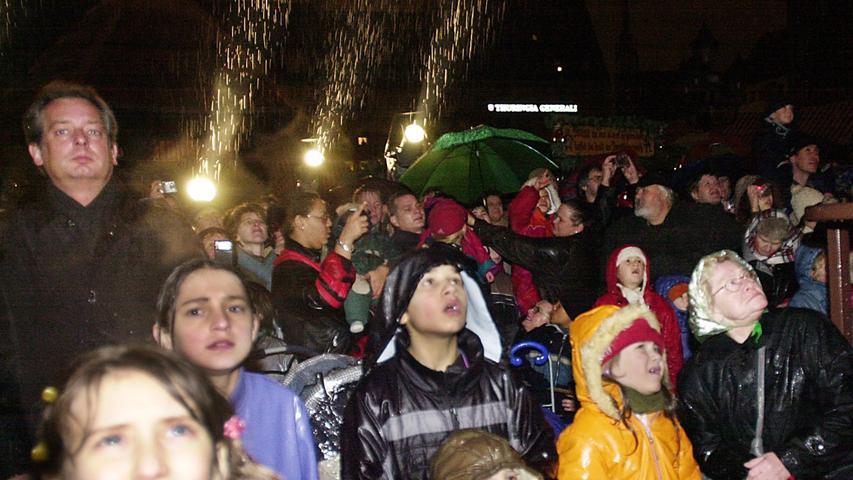 Trotz des Regens beobachten Kinder und Erwachsene gebannt die Eröffnung des Christkindlesmarktes 2003. Den Prolog sprach Christin Strauber.