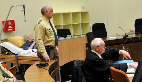 Umringt von Polizisten liegt der Angeklagte Rudolf U. bei der Fortsetzung des Prozesses wegen Mordes an einem jungem Staatsanwalt in Dachau in einem Krankenbett im Gerichtssaal.