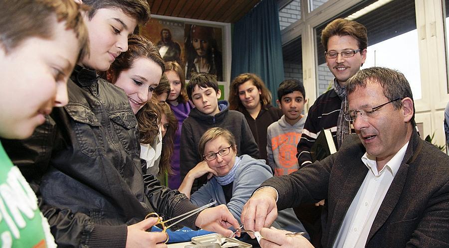 Malik hilft dem Kinderchirurg Karl Bodenschatz beim Nähen. Der Arzt zeigte den Schülern an einer Plastikhülle, wie eine Beschneidung abläuft. Bei der Diskussion auch dabei: Barbara Ameling vom Deutschen Kinderschutzbund und Fikret Bilir von der Ditib-Gemeinde.