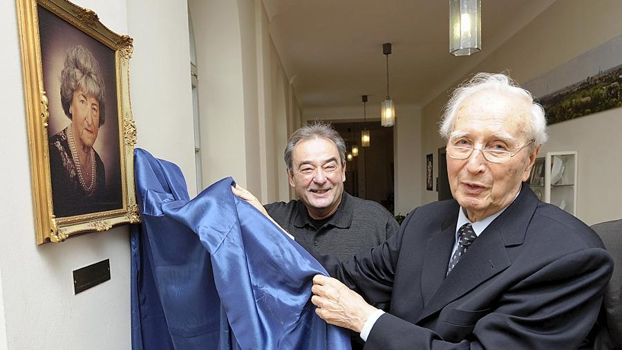 Stiftungsvorstand Hatto Bauer (vorne) enthüllte gemeinsam mit Günter Leupold, dem Neffen des Stifterpaars, im Flur des Fürther Rathauses das Bildnis von Anna Leupold.
