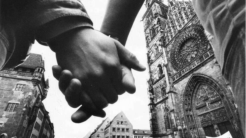 Während der Aktionswoche für den Frieden bilden kirchliche Mitarbeiter einen Schweigekreis gegen die Aufrüstung: Eine Stunde lang schweigen sie Hand in Hand vor der Lorenzkirche für den Frieden.