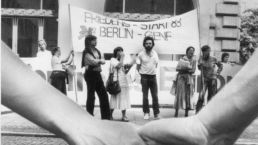 Friedensmarschierer stehen in Nürnberg Hand in Hand im Kreis um die Stadträte.