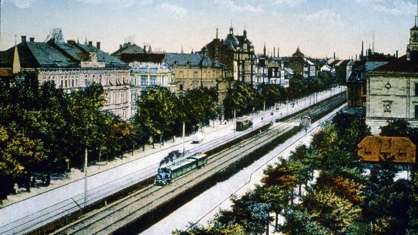 Diese Postkarte von 1905 zeigt die Begegnung von Eisenbahn und Straßenbahn. Letztere war seit den 1880er Jahren in Betrieb. Links und rechts der Schienen waren die Fahrbahnen, unter den Bäumen konnten die Fußgänger flanieren und dabei die prächtigen Fassaden der Bürgerhäuser bewundern.