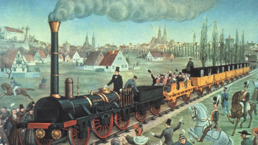 Die Ludwigs-Eisenbahn war die erste Eisenbahnlinie in Deutschland. Sie führte von Nürnberg nach Fürth und verlief parallel zur Fürther Straße. Hier zu sehen ist die Jungfernfahrt des
