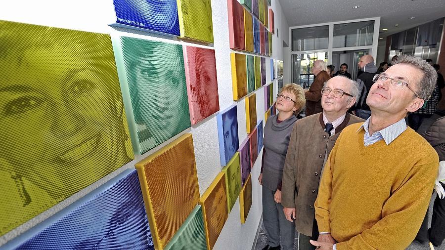 Freuen sich, Teil des Kunstwerks zu Ehren von Alfred Nathan geworden zu sein: Rudolf Ullrich (vorne) mit seiner Zwillingsschwester Eva Lippmann (hinten) und Vater Herbert Ullrich vor dem Wandmosaik der Frauenklinik.