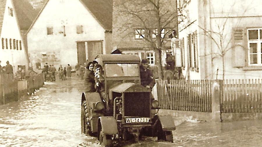 Hochwasser von 1940 in der Bachstraße: Fahrer Katheder steuert den  Flugplatztraktor durch die Fluten,  vorne rechts das Eckhaus Bachstraße/Rothenburger Straße. Heute ist dort das Ausstellungslager  der  Firma Weber.