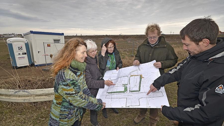 Parteimitglieder der Fürther Grünen studieren auf dem Baugelände einen Plan mit den Zufahrten. Vor allem die Verkehrsanbindung des Westens halten sie für unzureichend.
