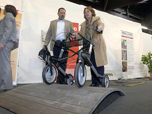 Auf der Inviva testet Marga Fritzsche einen Rollator. Udo Spielberger  erklärt die Unterschiede der verschiedenen Modelle.