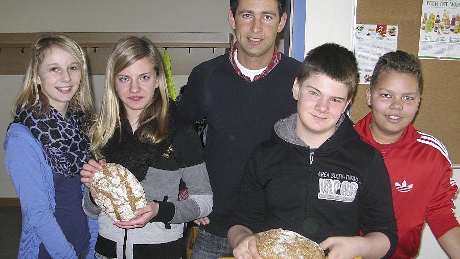 Schüler der Klasse 6a bereiten gemeinsam mit ihrem Lehrer Christian Herpolsheimer die Ausgabe der Brote vor.