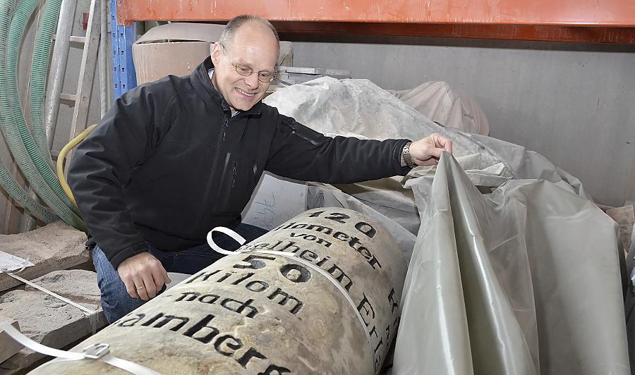Steinmetzmeister Roland Meier packt die bei einem Unfall auf der Poppenreuther Brücke zerbrochene und nun wieder zusammengefügte und gereinigte Sandsteinsäule in Plastikfolie ein.