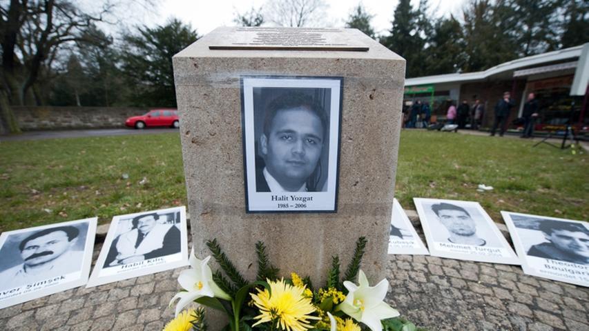 Kassel gedenkt dem mutmaßlichen NSU-Opfer mit einem Gedenkstein. Hinter dem Mahnmal sind die Porträts der anderen Mordopfer abgelegt.