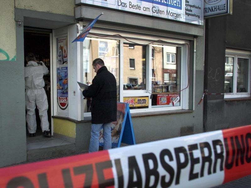 Polizeibeamte suchen nach dem Mord an Mehmet Kubasik in seinem Kiosk in Dortmund nach Spuren (Foto vom 04.04.2006).