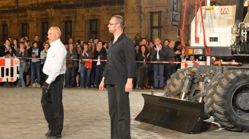 Tanz mit einem Bagger auf dem Erlanger Schlossplatz: Neben dem Tänzer Philippe Priasso (links) verneigte sich der virtuose Baggerfahrer William Defresne, beide von der Compagnie Beau Geste.