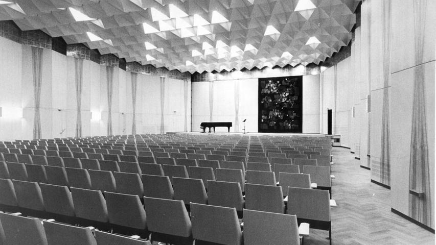 Helle Wandverkleidung, weiße Stuckkörperdecke und braunviolett bezogene Sitze: der kleine Saal.