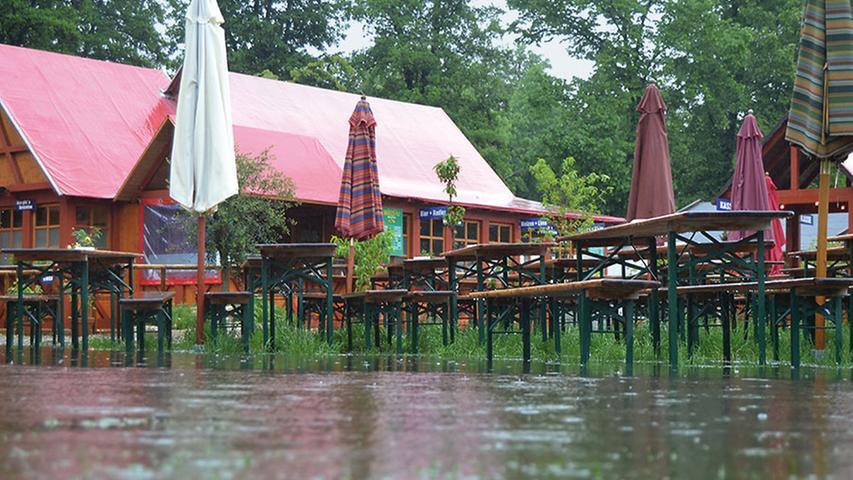 Auch die Bänke stehen unter Wasser. Sitzen kann man hier nur noch mit Regenmantel und Gummistiefeln.