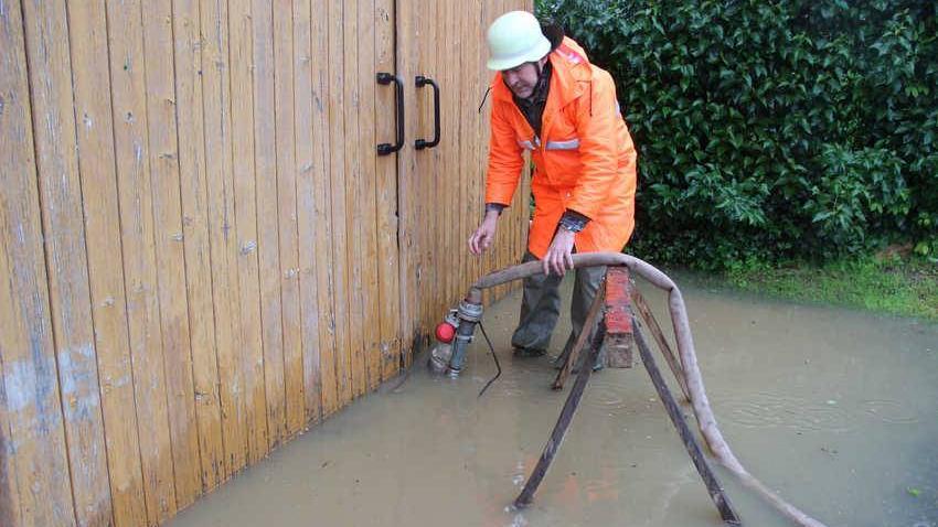 Mit einer Tauchpumpe versucht Feuerwehrmann Manfred Ficht den Wasserstand in der Scheune auf gleichem Niveau zu halten.