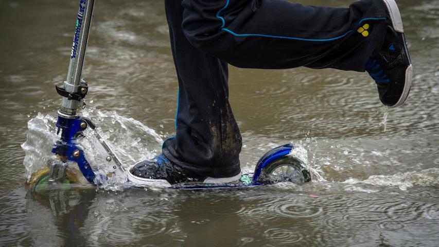 Ein Kind fährt mit einem Roller durch die überfluteten Straßen der Kreisstadt.
