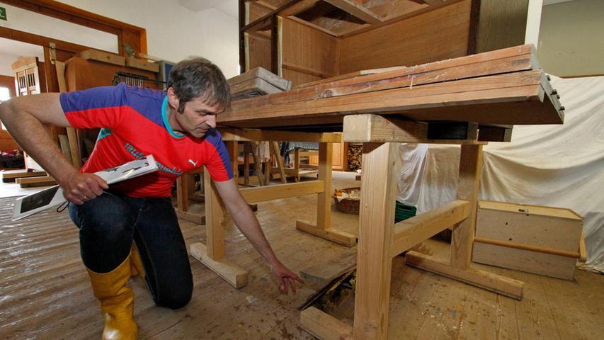In der Schreinerei steht unter dem Holzboden noch das Wasser, wie Einrichtungschef Michael Thiem demonstriert.