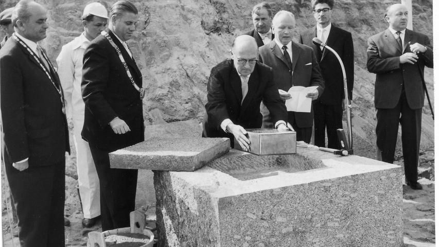 Baureferent Heinz Schmeißner versenkt die Kupferkassette mit dem großen Stadtwappen in den Grundstein, Oberbürgermeister Dr. Urschlechter (Zweiter von links) rüstet sich für die Hammerschläge.