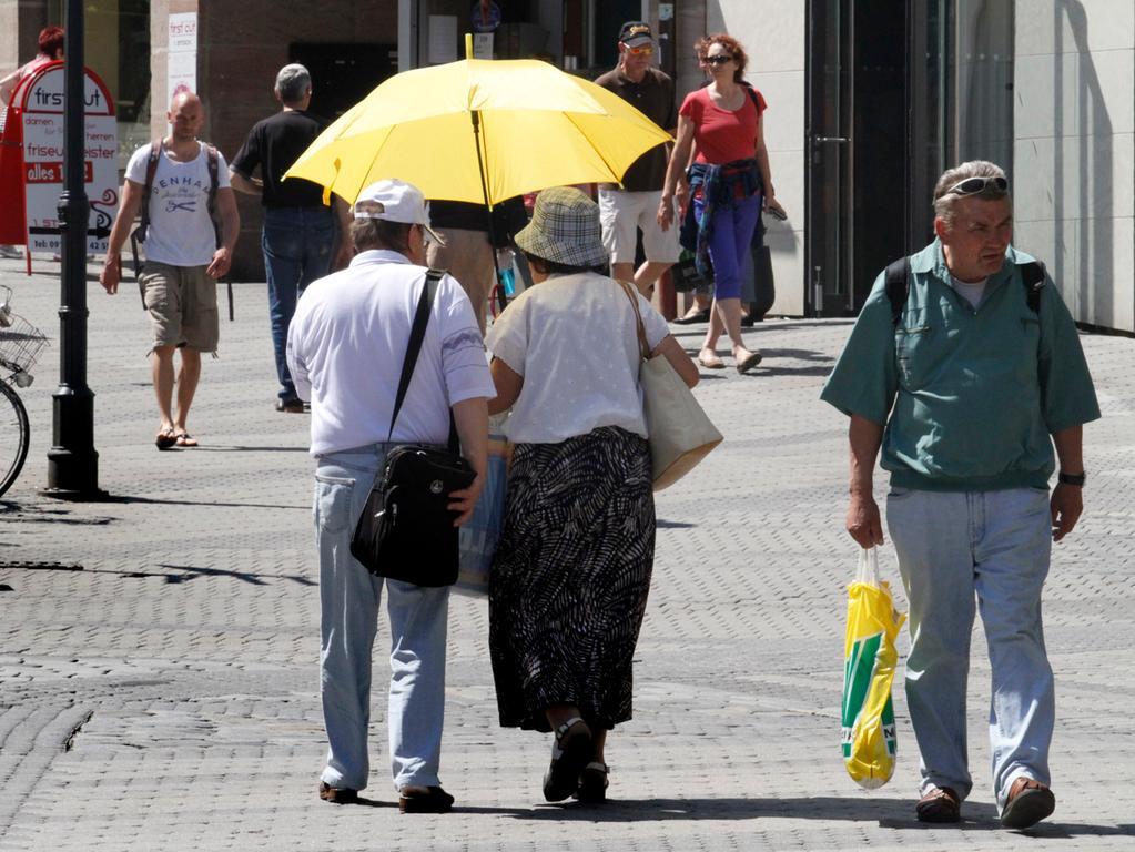 Ein seltenes Bild in diesem Sommer: Diese Besucher in Nürnbergs Innenstadt haben den Regenschirm kurzerhand umfunktioniert.