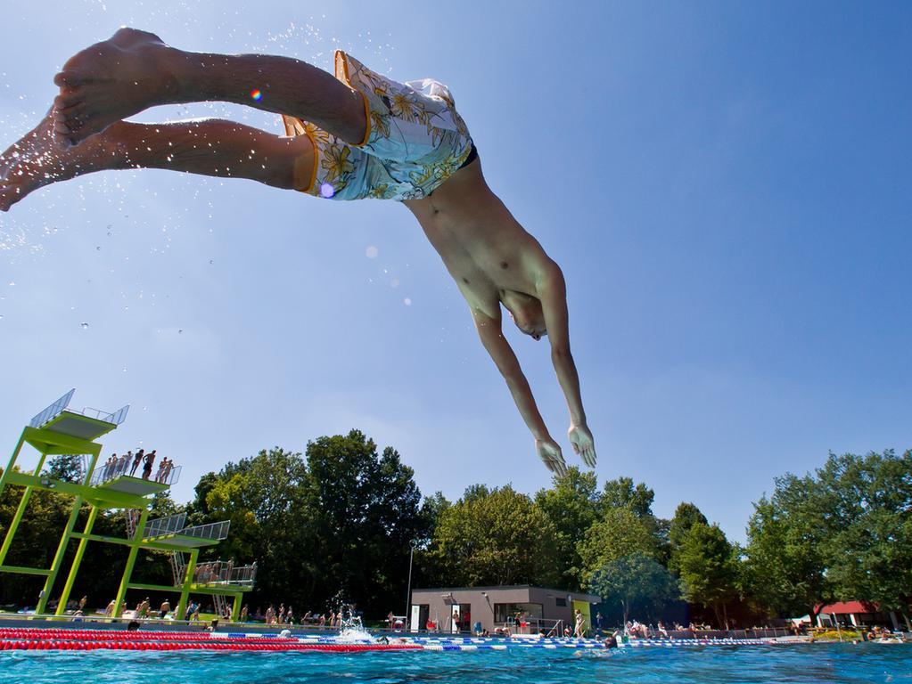 Ein Junge springt am Mittwoch (01.08.2012) in einem Freibad in Nürnberg  (Mittelfranken) ins Wasser. Sommerliche Temperaturen bis zu 30 Grad locken  zahlreiche Menschen ins Schwimmbad. Foto: Daniel Karmann dpa/lby +++(c) dpa -  Bildfunk+++