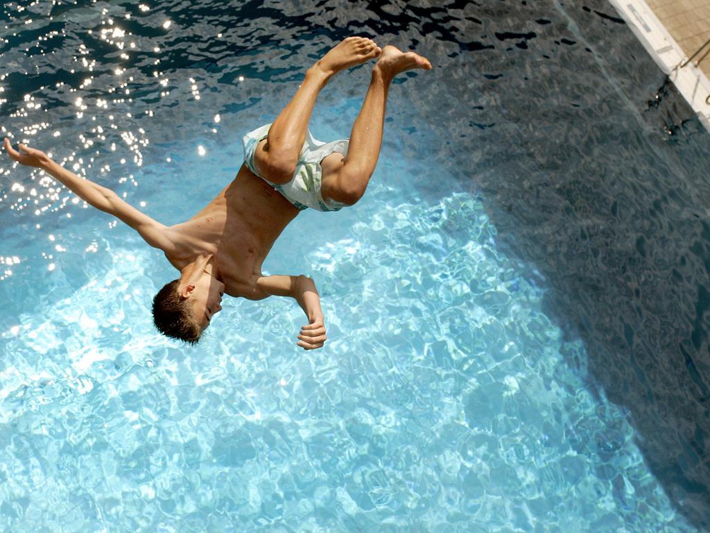 Ein Junge springt am Dienstag (18.08.2009) im Stadionbad in Nürnberg  (Mittelfranken) ins Becken. Laut Vorhersage der Meteorologen bleibt das Wetter  in Bayern die gesamte Woche über heiß und sonnig. Foto: Daniel Karmann dpa/lby  +++(c) dpa - Bildfunk+++