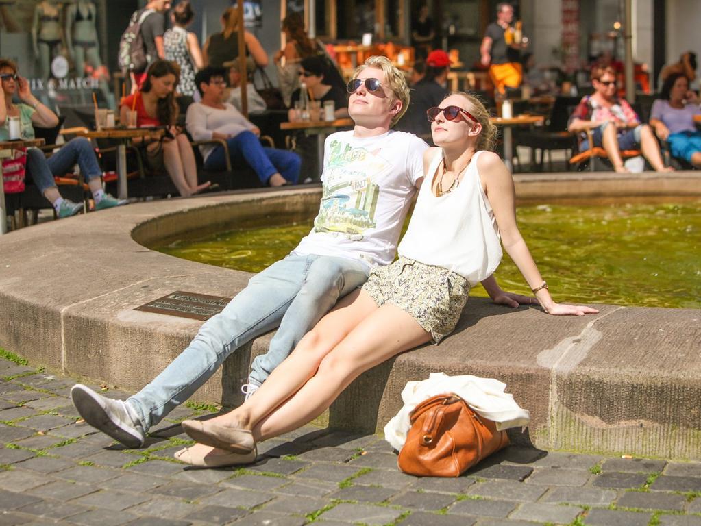 Julian (22) und Christine (22) aus Nuernberg sonnen sich an einem Brunnen am  Weissen Turm am Donnerstag (13.06.2013) in Nuernberg. In Nuernberg wurde heute  teilweise 29 Grad gemessen. Viele Nuernberger geniesen die Sonne in der Stadt.  Foto: News5 / Mahler