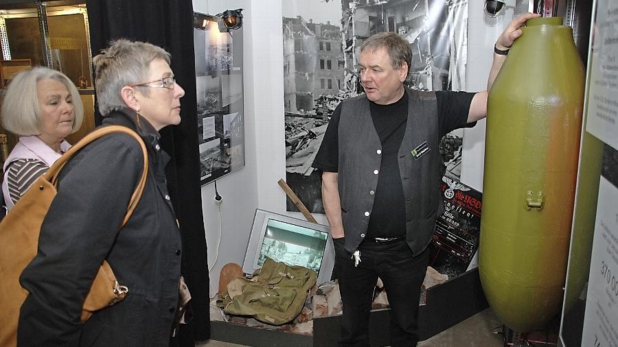 """Museumsmacher Gerd Walther, der hier 2012 Besucherinnen die Weltkriegsausstellung """"Die Bombe"""" erläutert, ließ kurz vor dem Ende seiner Amtszeit mit einer Streitschrift zur Neuorganisation eine Bombe platzen."""