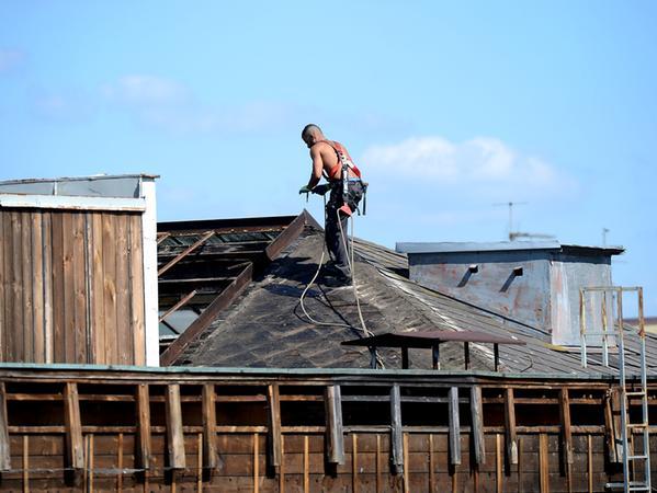 Bauarbeiter haben am Montagvormittag die Glasscheiben und die ersten Schindeln abgenommen und ins Gebäudeinnere geworfen.