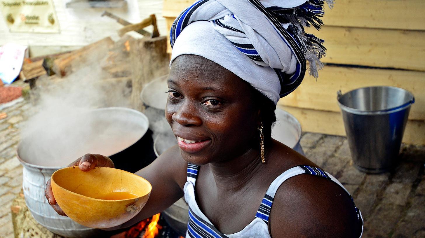 """""""In Burkina Faso ist Bierbrauen Frauensache"""": Ine Kam trinkt aus einer Schale Hirsebier."""