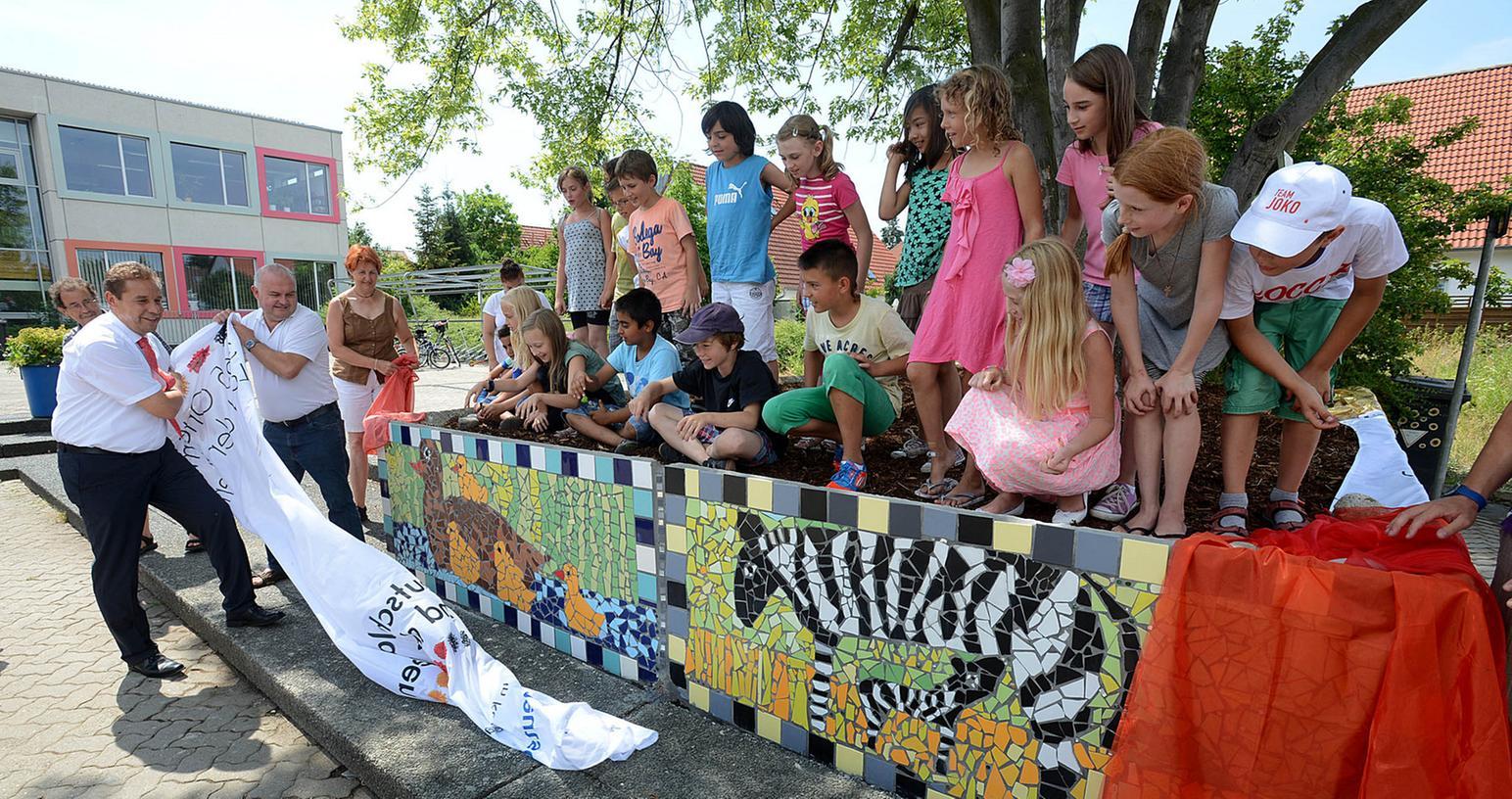Stolz schauen die kleinen Künstler der Stadelner Hans-Sachs-Grundschule zu, wie  Bürgermeister Markus Braun und Sponsor Andreas Landgraf das Mosaik enthüllen.