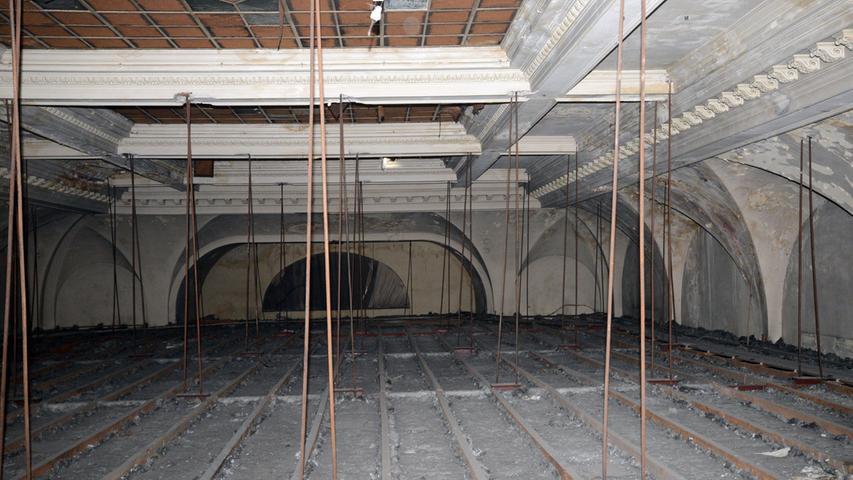 Bis vor kurzem war der Blick auf die historische Decke (oben) durch eine abgehängte Zwischendecke (unten) versperrt, die einst zur Abdunkelung des Raums für den Kinobetrieb angebracht wurde.