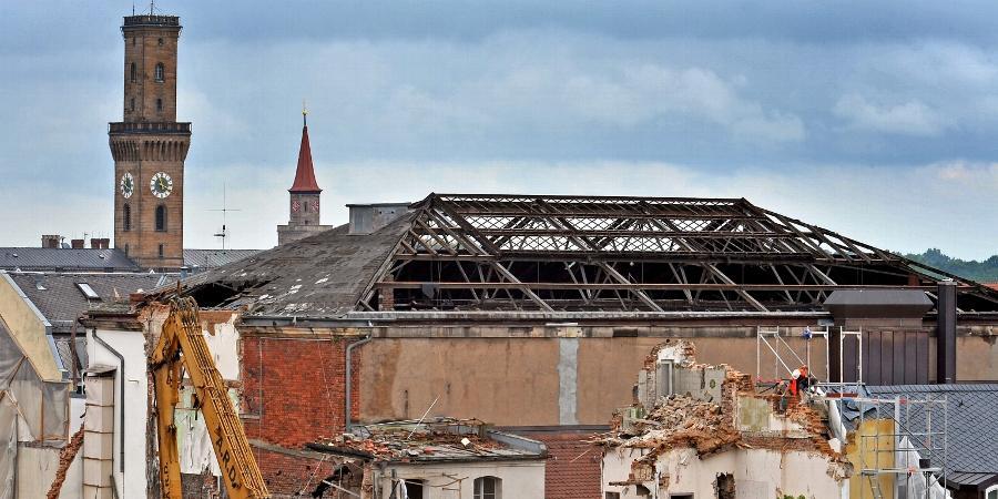 Das Park-Hotel ist aus dem Stadtbild verschwunden. Nur die Wand zum Nachbarhaus muss noch händisch abgetragen werden (rechts unten). Durch den Abriss des Hotels ist der Blick auf den großen Backsteinbau frei geworden, der den Festsaal beherbergt. Das Dach ist schon nicht mehr heil.