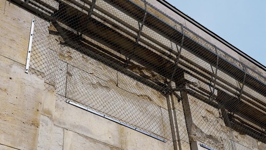 Sicherungsmaßnahmen durch Gittergewebe an den Mauervorsprüngen sollen den weiteren Verfall verlangsamen und vor herabstürzenden Brocken schützen.