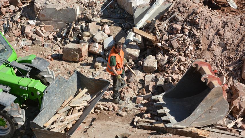 Es gibt viel zu tun für die Arbeiter auf der Baustelle in Fürths Mitte. Händisch sortieren die Männer Holz aus dem Schutt.