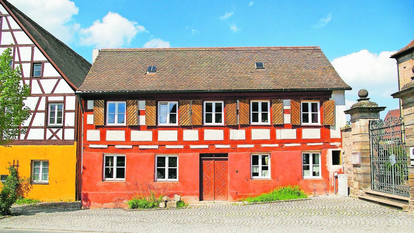 """Das """"Mesnerhaus"""" in der Nürnberger Straße in Schwand. Links das mächtige """"Richterhaus"""", rechts die Friedhofsmauer. Auch wenn es so aussieht: das """"Mesnerhaus"""" ist nicht an die Friedhofsmauer angebaut, allerdings ist der Spalt zwischen Haus und Friedhofsmauer zugemauert."""
