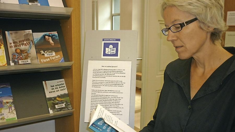 """Die Leiterin der Stadtbibliothek Anne Grimmer wirft einen Kontrollblick auf den neuen Bestand """"Leichte Sprache""""."""