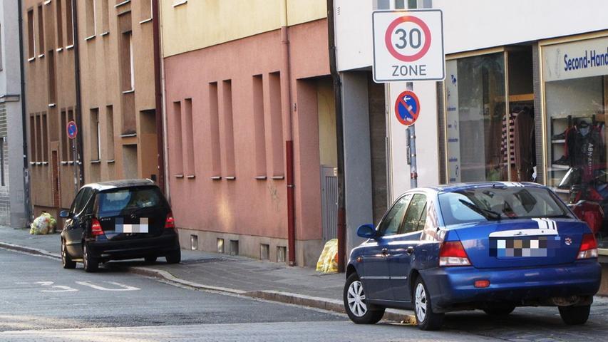 Diese beiden, halbseitig auf dem Gehweg stehenden Autos sehen nicht danach aus, als ob sie be- oder entladen werden. Da wäre also ein Bußgeld fällig. Wenn Sie nun meinen, dass der Halter des rechten Autos ohne Bußgeld davonkommt, weil er ja VOR dem eingeschränkten Halteverbot steht, dann liegen Sie übrigens falsch, denn...