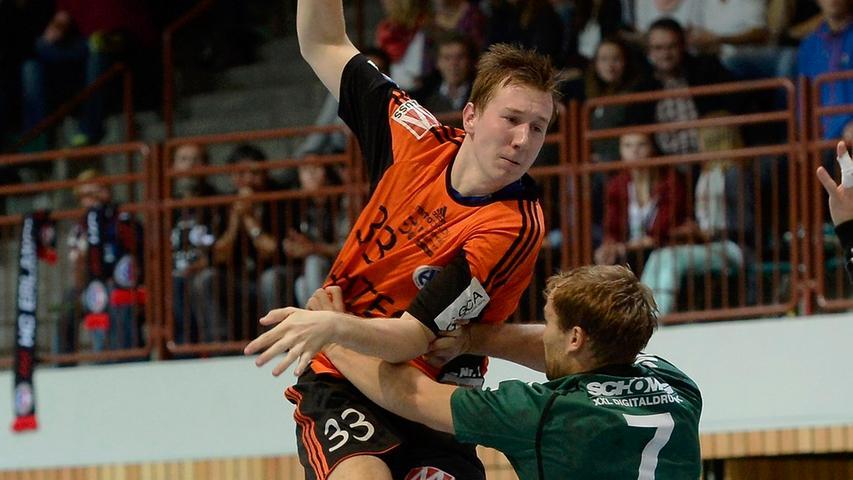 Die Erlanger in orangenem Trikot lieferten sich ein spannendes Match mit den Wölfen. Hier: Nikolai Link (HCE) gegen Stefan Schmitt.