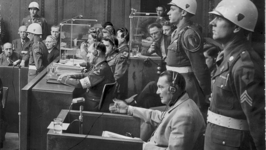 Der Hauptkriegsverbrecher Hermann Göring auf dem Zeugenstuhl, flankiert von MP-Soldaten. Er wurde am Ende des Prozesses zum Tode verurteilt, schaffte es aber einige Stunden vor dem Tod durch den Strang, sich mit einer Zyankalikapsel selbst zu töten.