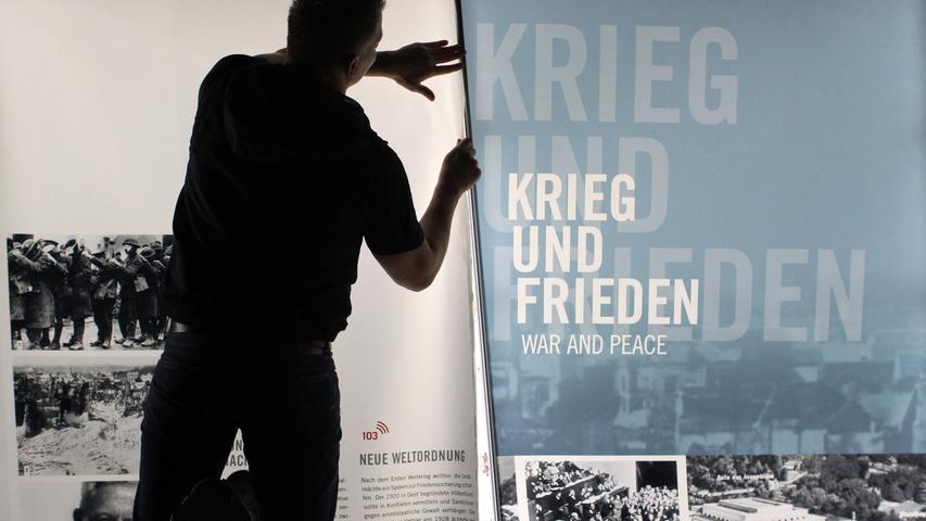Ein Mann befestigt die letzten Schautafeln im Museum
