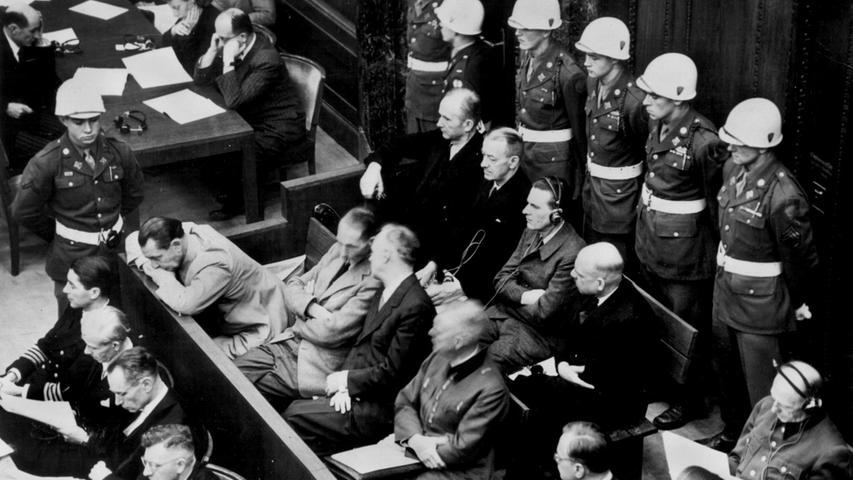 Am 20. November 1945 wurde der Hauptkriegsverbrecherprozess gegen führende NS-Größen in Nürnberg eröffnet. Am ersten Tag des Hauptprozesses hören die Angeklagten vor dem internationalen Militärgericht die Verlesung der Anklageschrift im Gerichtssaal des Nürnberger Justizpalastes. In der zweiten Reihe sitzen (v.l.) Hermann Göring, Rudolf Hess, Joachim von Ribbentrop, Wilhelm Keitel, Alfred Rosenberg und Hans Frank. In der hinteren Reihe sind (von links) die Angeklagten Karl Dönitz, Erich Räder, Baldur von Schirach, Fritz Sauckel und Alfred Jodl zu sehen. Die Verteidiger sitzen vor den Angeklagten.