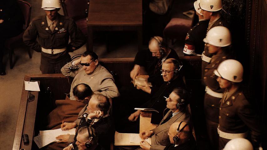 Der Mann mit der Sonnenbrille ist der frühere Reichsmarschall Hermann Göring, gleich neben ihm der einstige Stellvertreter des Führers, Rudolf Heß. Göring schützt seine Augen vor den 22 Deckenstrahlern, die den Saal für die Prozess-Filmaufnahmen ausleuchteten.