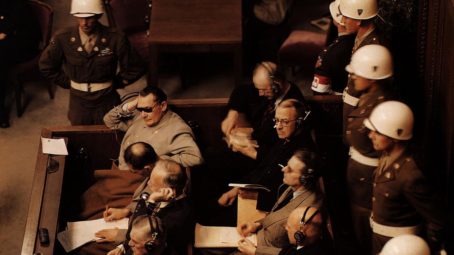 Einer der Hauptangeklagten bei den Nürnberger Prozessen war der frühere Reichsmarschall Hermann Göring (mitSonnenbrille). Gleich neben ihm der einstige Stellvertreter des Führers, Rudolf Heß. Göring schützt seine Augen vor den 22 Deckenstrahlern, die den Saal für die Prozess-Filmaufnahmen ausleuchteten.