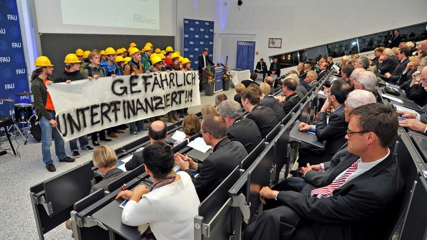 Während Bernd Sibler, Staatssekretär vom Ministerium für Kultus und Wissenschaft, gerade mit seiner Rede ansetzen will, marschieren die Studenten die Treppe herunter zum Rednerpult. Ein paar Minuten lang verharren sie dort stumm, bis sie unter Applaus wieder abziehen.