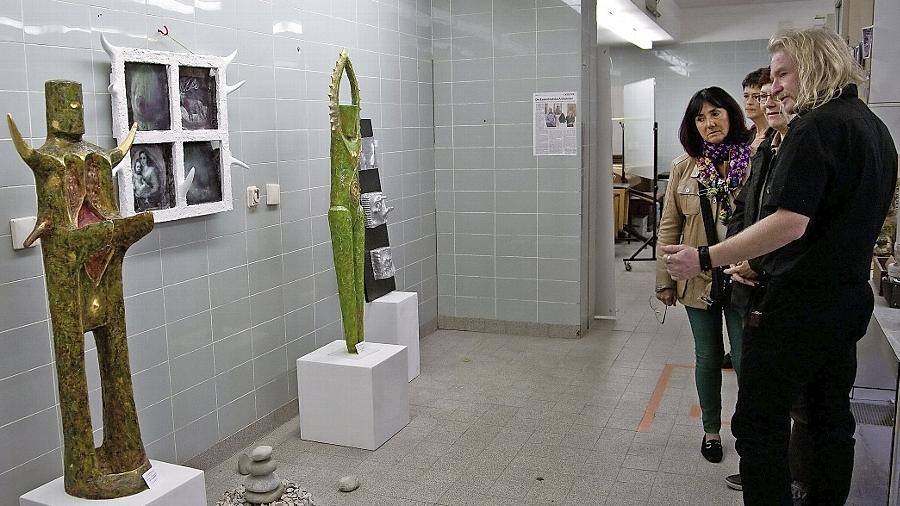 In dem noch vom Klinikflair angehauchten Kunstquartier auf Zeit erläutert der Bildhauer Richard Bartsch (vorne) Besucherinnen seine Skulpturen.