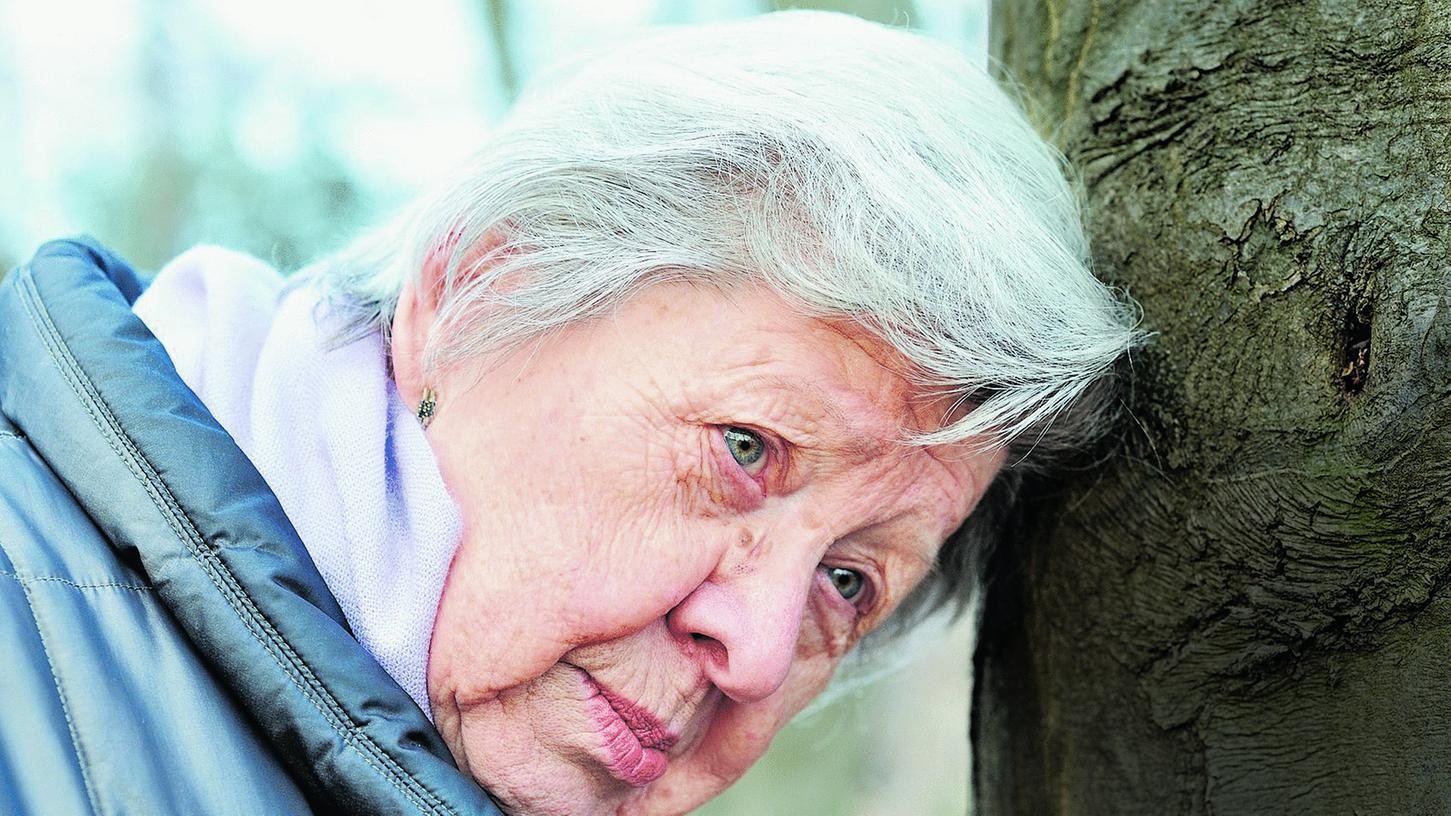 Die Suche nach Erinnerung: Eine alte Frau lehnt ihren Kopf nachdenklich an einen Baum.