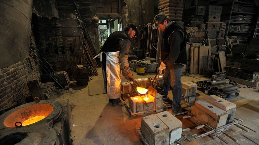 In Teamarbeit werden die vorbereiteten Gussformen mit der flüssigen Bronze befüllt.